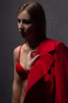 Giovane donna in biancheria intima e cappotto