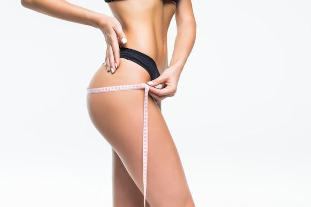 Giovane donna in biancheria intima nera che misura la sua vita con metro a nastro.