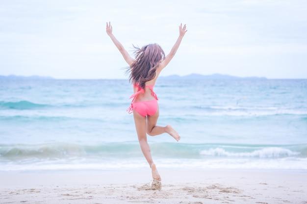 Giovane donna in bikini che salta sulla spiaggia di sabbia e onde e relax, concetto di viaggio estivo.