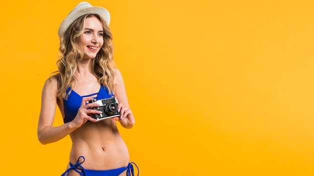 Giovane donna in bikini, mantenendo la fotocamera