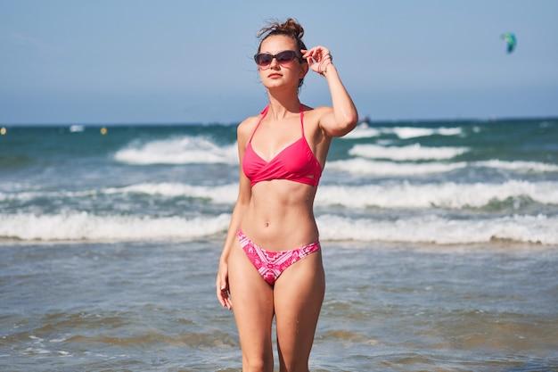 Giovane donna in bikini rosa che posa in un mare.