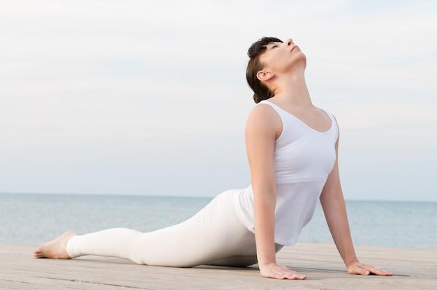 Giovane donna in buona salute che fa posizione di yoga in mare: posa della cobra