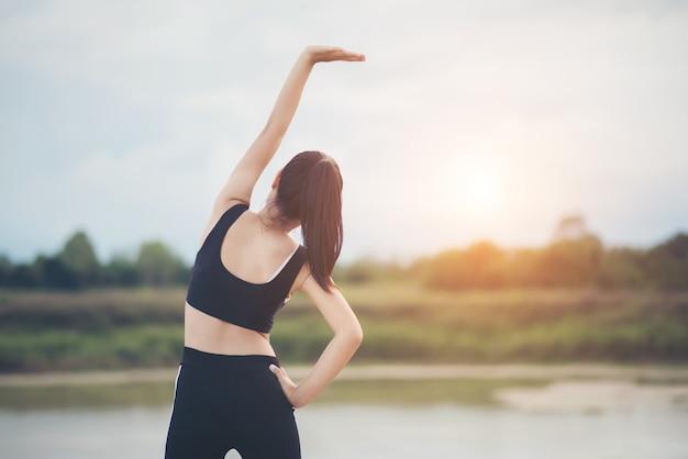Giovane donna in buona salute che si scalda allenamento all'aperto prima dell'allenamento al parco.