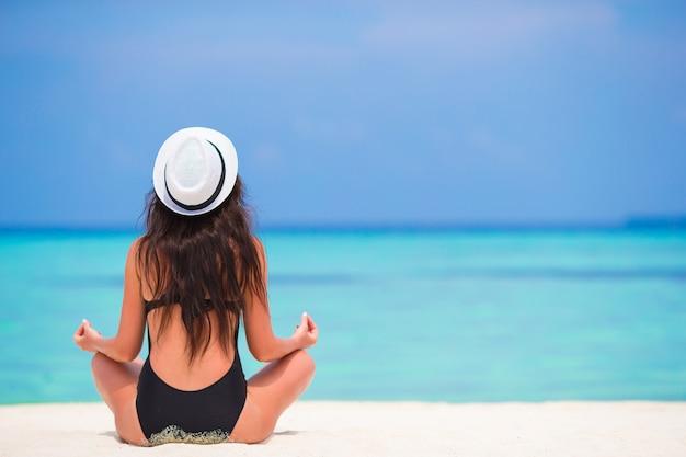 Giovane donna in buona salute che si siede nella posizione di yoga che medita su spiaggia