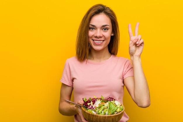 Giovane donna in buona salute che tiene un'insalata che mostra numero due con le dita.