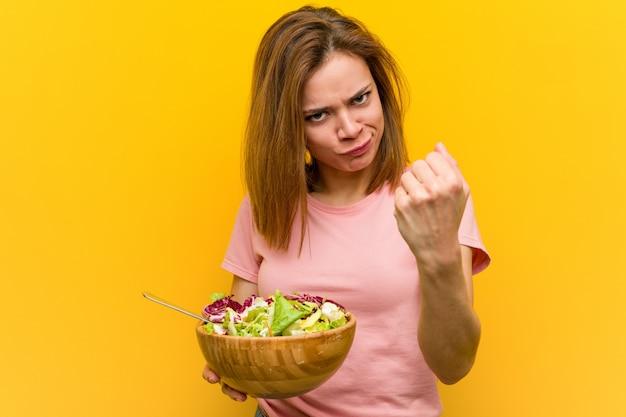 Giovane donna in buona salute che tiene un'insalata che mostra pugno con con espressione facciale aggressiva.