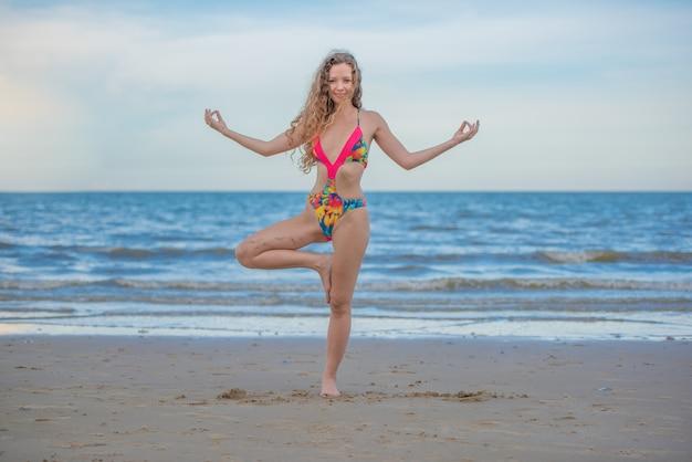 Giovane donna in buona salute con capelli ricci biondi che praticano yoga sulla spiaggia, vacanza al mare di estate e concetto di rilassamento.