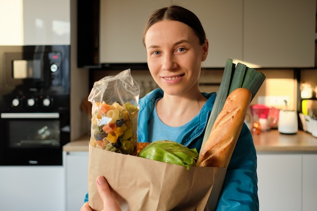 Giovane donna in buona salute con i sacchetti della spesa a casa