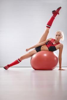 Giovane donna in buona salute e sportiva che si esercita sulla palla di forma fisica al