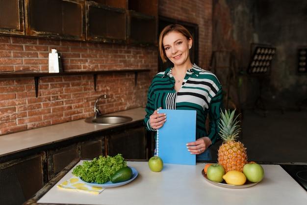 Giovane donna in buona salute splendida che mangia mela nella sua cucina moderna del sottotetto. allenatore di fitness