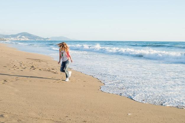 Giovane donna in camicia a scacchi rossa, jeans, scarpe da ginnastica bianche che cammina lungo la spiaggia e l'oceano tempestoso in giornata di sole invernale
