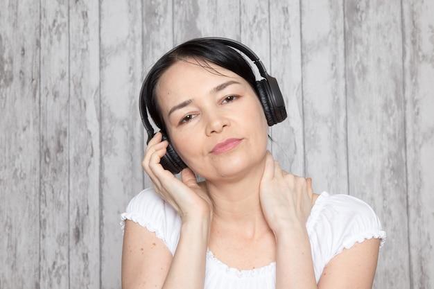 Giovane donna in camicia bianca ascoltando musica in cuffia nera sul muro grigio