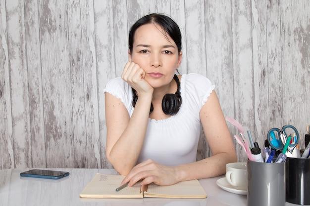 Giovane donna in camicia bianca, bere caffè ascoltando musica in cuffia nera scrivere note sul muro grigio