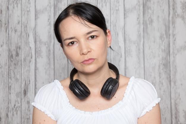 Giovane donna in camicia bianca scontenta del muro grigio