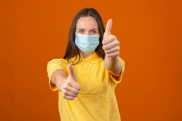 Giovane donna in camicia di polo gialla e maschera protettiva medica che mostra pollice sul segno che guarda l'obbiettivo con espressione positiva su sfondo arancione