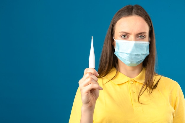 Giovane donna in camicia di polo gialla e maschera protettiva medica tenendo il termometro in mano guardando la telecamera con la faccia seria su sfondo blu isolato