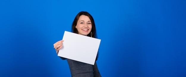 Giovane donna in camicia grigia che tiene un foglio di carta e uno sguardo