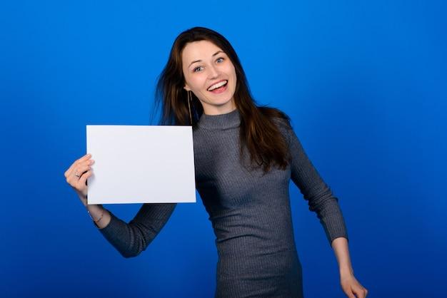 Giovane donna in camicia grigia in possesso di un foglio di carta e guardando la telecamera, sorridente. sfondo blu isolato