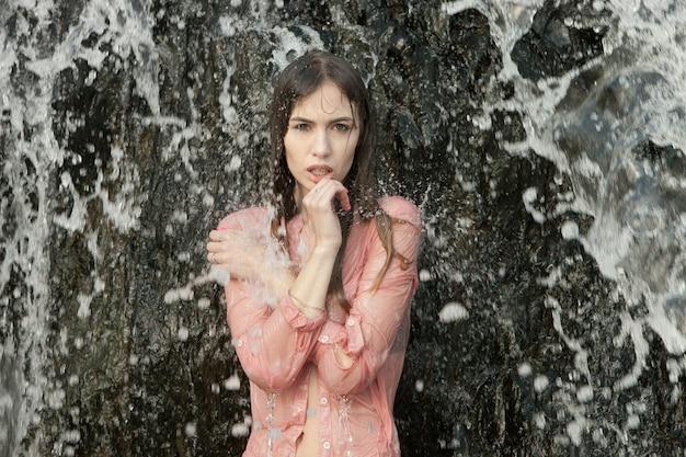 Giovane donna in camicia rosa si trova sotto getti wate a cascata