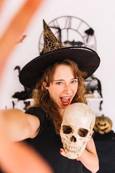 Giovane donna in cappello a punta tenendo il cranio