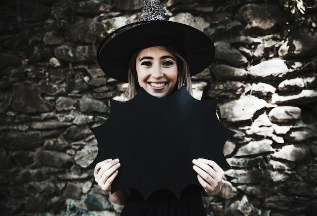 Giovane donna in cappello della strega che tiene decorazione e sorridere di halloween