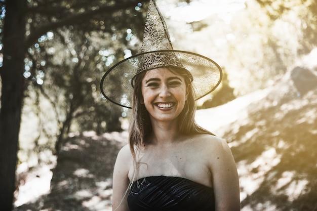Giovane donna in cappello della strega in piedi nella foresta e sorridente