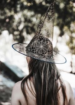 Giovane donna in cappello della strega in piedi nella foresta