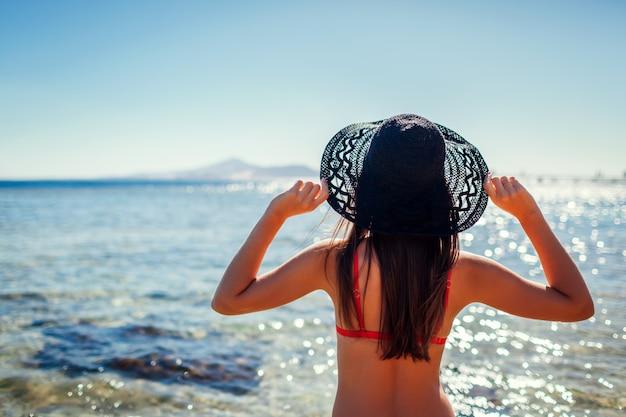 Giovane donna in cappello della tenuta del bikini sulla spiaggia dal mar rosso. concetto di viaggio e di vacanza