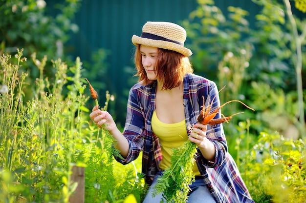 Giovane donna in cappello di paglia durante il tempo del raccolto