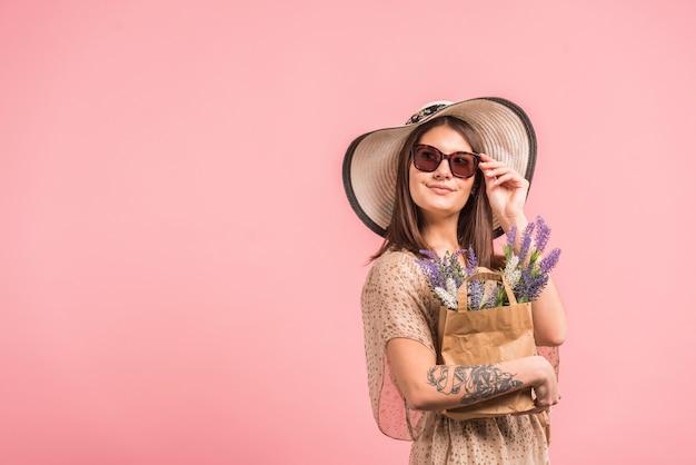 Giovane donna in cappello e occhiali da sole che tiene la borsa con i fiori