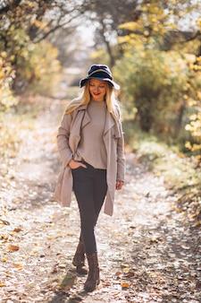 Giovane donna in cappello in un parco in autunno
