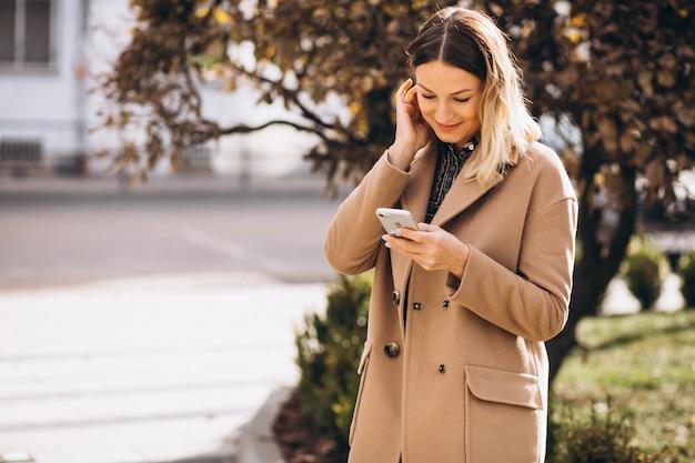Giovane donna in cappotto beige utilizzando il telefono fuori strada