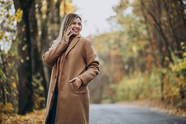 Giovane donna in cappotto che sta sulla strada in un parco di autunno