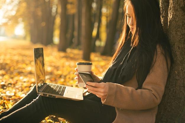 Giovane donna in cappotto con una tazza di caffè e laptop dello smartphone