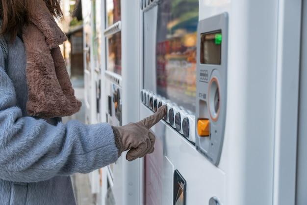 Giovane donna in cappotto e guanti invernali comprare acqua e dolci nel distributore automatico sulla strada durante una passeggiata nel parco cittadino.