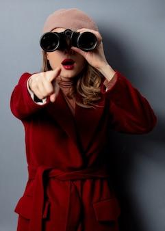 Giovane donna in cappotto rosso con il binocolo