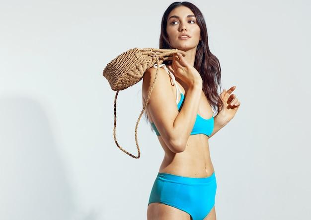 Giovane donna in costume da bagno blu su sfondo chiaro.