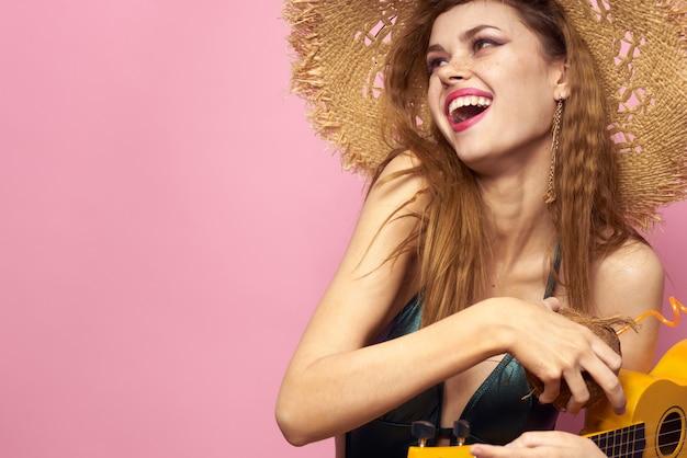 Giovane donna in costume da bagno e un cappello con ananas in mano, festa di divertimento, spiaggia a casa suonando la chitarra ukulele