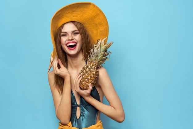 Giovane donna in costume da bagno e un cappello con ananas in mano