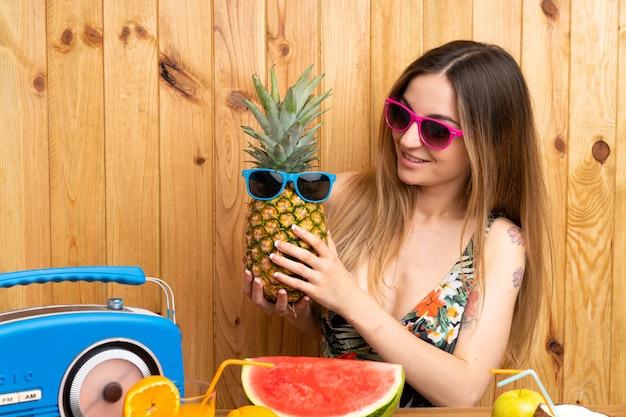 Giovane donna in costume da bagno in possesso di un ananas con occhiali da sole