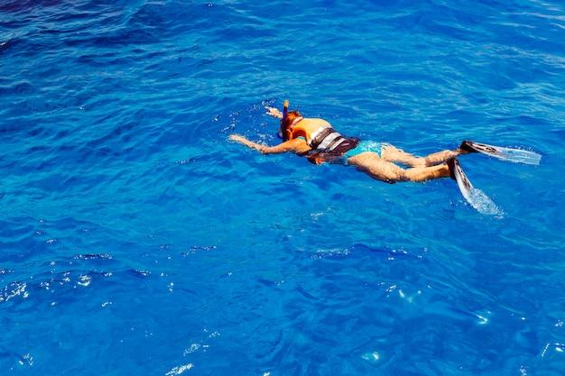 Giovane donna in costume da bagno lo snorkeling