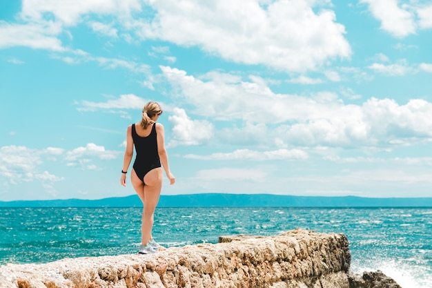 Giovane donna in costume da bagno nero e scarpe sportive in vacanza a piedi verso il mare blu