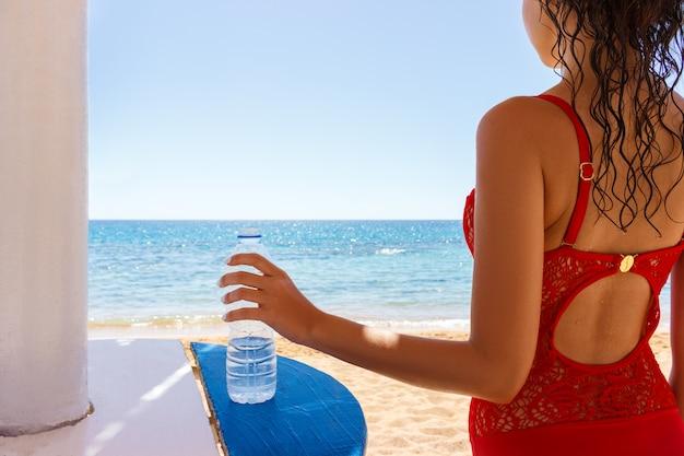 Giovane donna in costume da bagno rosso sulla spiaggia tenendo una bottiglia d'acqua