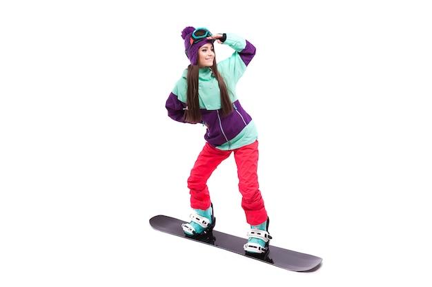Giovane donna in costume da sci viola giro snowboard