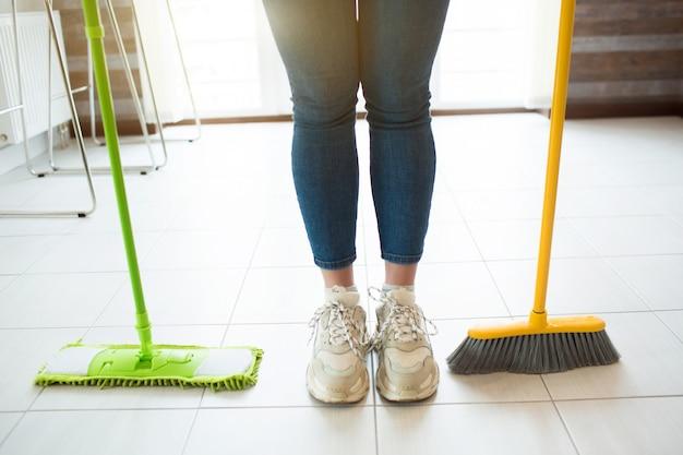 Giovane donna in cucina. stare sul pavimento con la scopa verde e la scopa gialla. tempo di pulizia alla luce del giorno. solo in cucina. taglia vista.