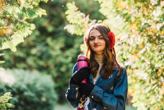 Giovane donna in cuffia che tiene thermos nel parco