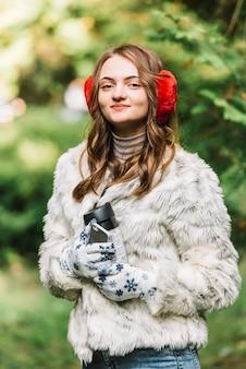 Giovane donna in cuffie che tiene smartphone e thermos