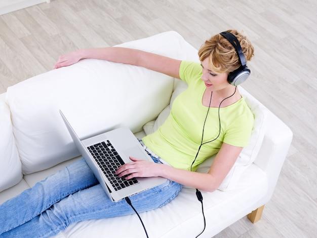 Giovane donna in cuffie con laptop rilassante sul divano - angolo alto