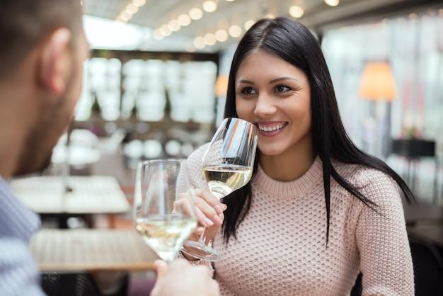 Giovane donna in data con l'uomo nella caffetteria, bere vino.