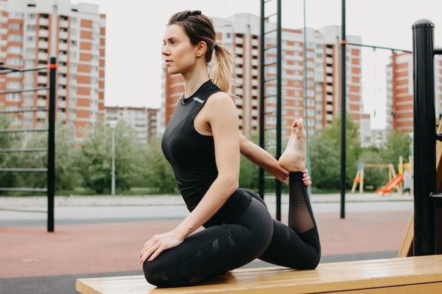 Giovane donna in forma attraente nello sport grigio indossare il riscaldamento facendo